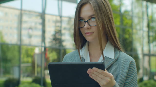 young startup businesswoman using digital tablet. beautiful woman in glasses texting messages, cheating on her digital tablet near office district. business. social networking. people. apps. - direttrice video stock e b–roll