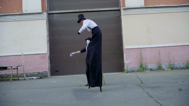 stockvideo's en b-roll-footage met jonge stilt imiteert oude man in de buurt van gebouw - vetschmink