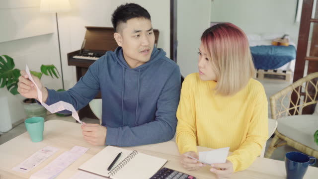 Young stressed asian couple managing finances, reviewing their bank accounts using laptop computer and calculator at modern home. Woman and man doing paperwork together, paying taxes online.