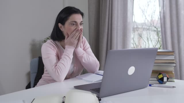 Young stressed Caucasian woman looking at laptop screen, shaking head and holding it with hands. Shocked brunette mother or wife found messages in social media. Lifestyle, peeking, privacy.