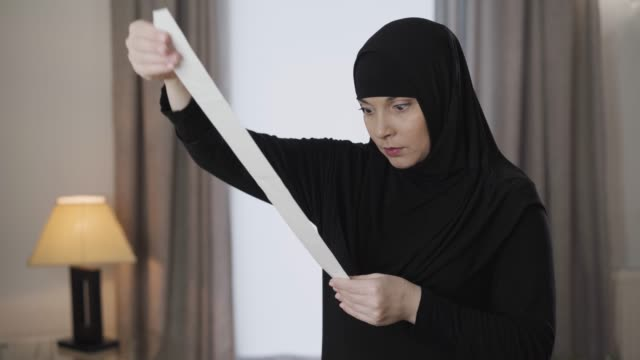 young stressed muslim woman in traditional hijab raising up bill and looking at it with shocked facial expression. young eastern lady dealing with receipts at home. lifestyle, muslim culture. - scontrino video stock e b–roll
