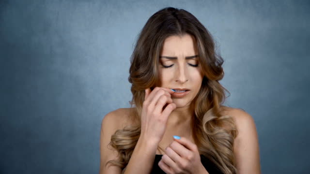 Young stressed woman biting her nails over grey background. video