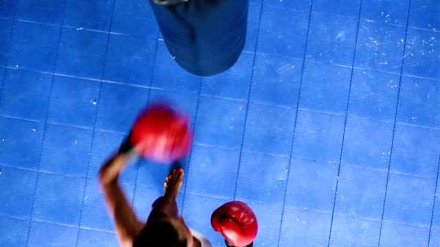 Young Strong Female Athlete Punching Body Bag Shot From Above Looking Down. Self Defense Training. video