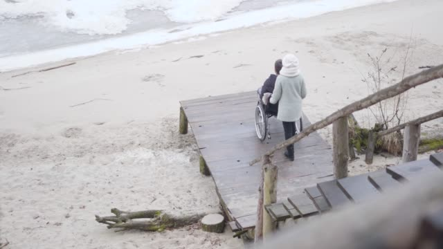 Young strong mother rolling wheelchair with disabled son along pier and talking to handicapped young man. Caucasian invalid tender spending autumn day with patient outdoors. Rehabilitation, leisure.