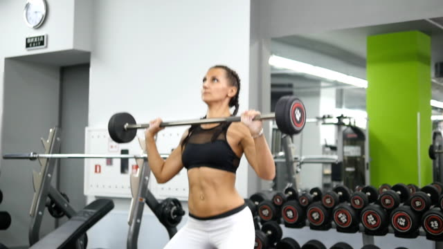 Young strong woman with perfect fitness body in sportswear snatches heavy weight in gym. Female bodybuilder doing exercise - practicing deadlift at club. Girl training - lifting barbell. Slow motion video