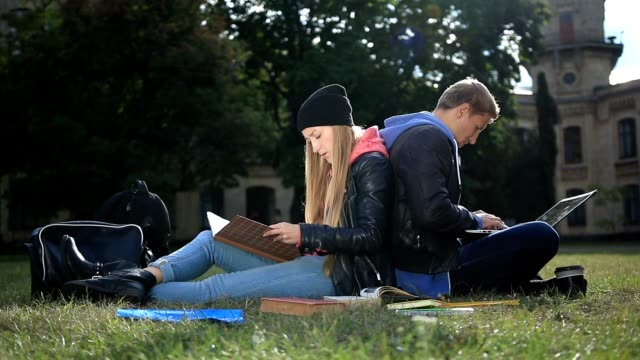 Young student couple studying in the park lawn video