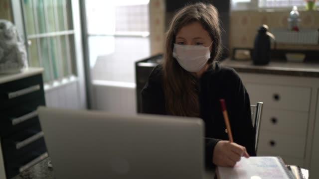 vidéos et rushes de jeune étudiant faisant des devoirs à la maison - homeschooling - chat vidéo - enfant masque