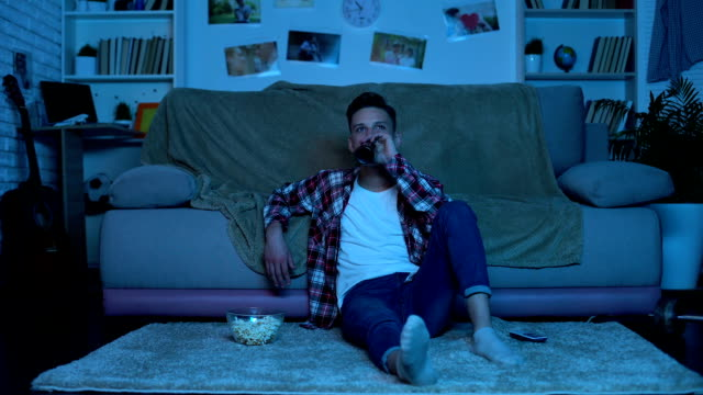 young student drinking beer and eating popcorn watching tv show, weekend leisure - divano procrastinazione video stock e b–roll