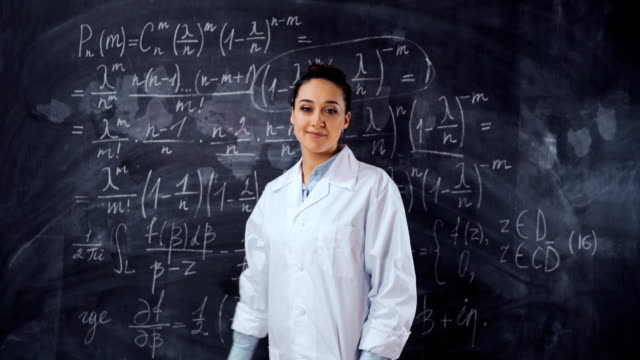 Young student female solve hard equation on black chalk board Young student female in white robe solve hard and heavy to understand math equation on black chalk board, She turn to camera and smile. Smart, clever, intelligent scientist woman concept. mathematics stock videos & royalty-free footage
