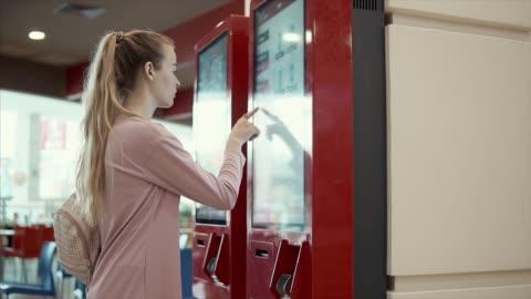 vídeos de stock e filmes b-roll de young student girl is choosing food in fast-food restaurant on big screen - consumismo