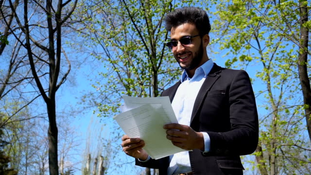 Young student reading diploma work and smile with dimples in slow motion video