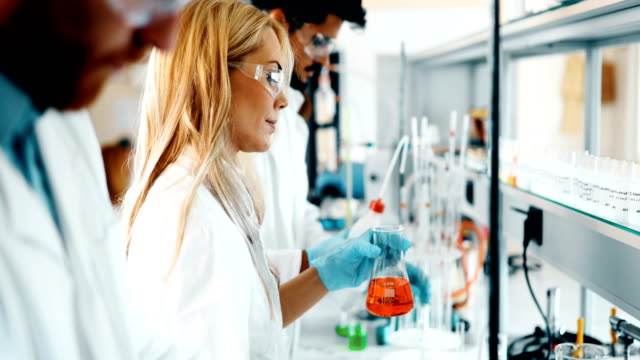 Young students of chemistry working in laboratory video