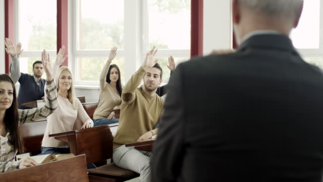 Young students raising hand to answer question video