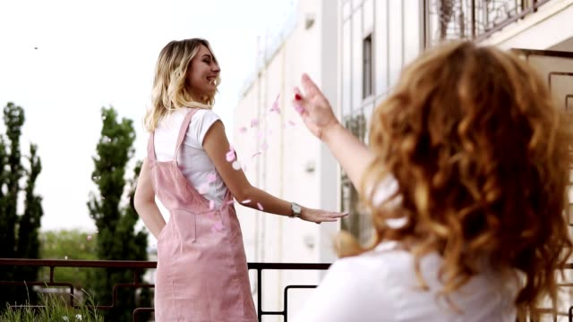young, stunning blonde girl is sprinkle the confetti out from the balcony. calling out for her girlfriends. everybody spread out the silver confetti. beautiful stylish women. hen party concept - bachelorette party stock videos & royalty-free footage