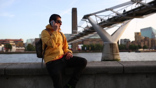 Young Stylish Adult Man With Yellow Jacket Sits On The Wall Near Thames River And Talks On The Mobile Phone Nodding With His Head