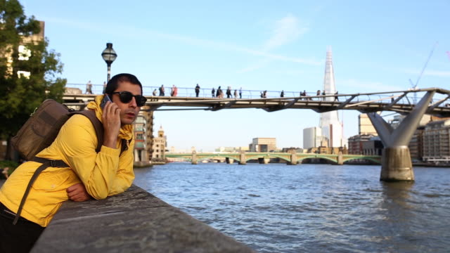 Young Stylish Adult Man With Yellow Jacket Talking On The Mobile Phone And Nodding With His Head