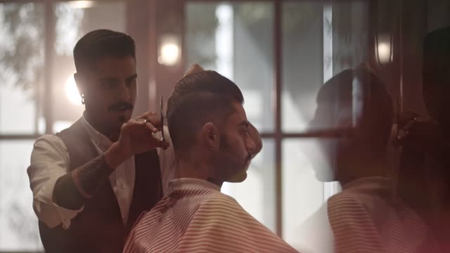 Young stylish barber cutting client's hair in old-fashioned barber shop video