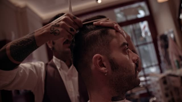 Young stylish barber giving man haircut in old-fashioned barber shop video