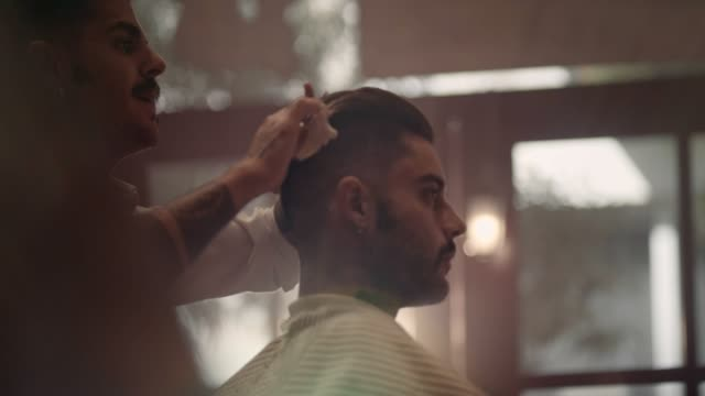 Young stylish barber with tattoos cutting and styling man's hair video