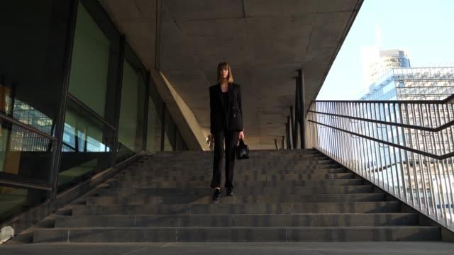 unga snygga business kvinna gick nedför trapporna - kostym sida bildbanksvideor och videomaterial från bakom kulisserna
