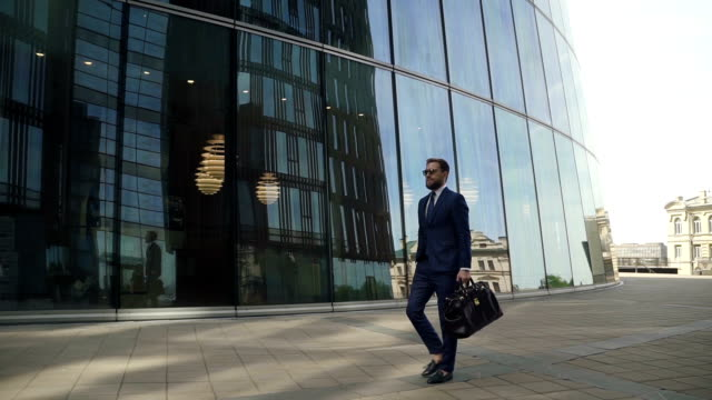 Young stylish businessman is walking along street on modern building background Young stylish businessman is walking along street on modern building background, rich business owner with leather bag in hand, is going confidently, looking at watch in summer day. Concept: entrepreneurship, business, lifestyle. handsome people stock videos & royalty-free footage