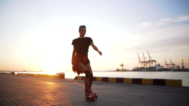 young stylish funky girl with green hair riding roller skates and dancing near sea port during sunset, slow motion - lama oggetto creato dall'uomo video stock e b–roll