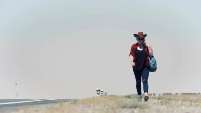 Young stylish girl in cowboy clothes doing hitch-hiking in desert, on the road. She carries backpack and hat. Pass trucks, delivery trucks. California or Nevada. Search yourself, escape from problems. video