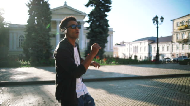 Young stylish hipster black man in white headphones and sun glasses dancing outdoor in city centre, having some fun video