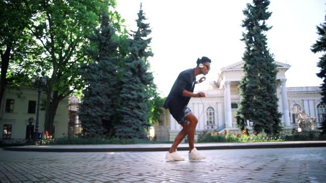 ung snygg hipster svart man i vita hörlurar och solglasögon dans utomhus i centrum, ha lite kul - street dance bildbanksvideor och videomaterial från bakom kulisserna