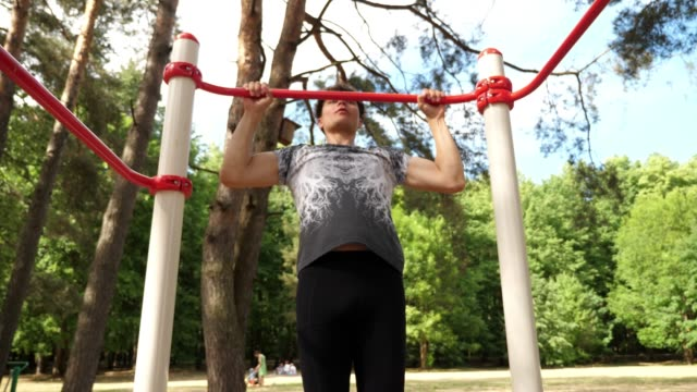Young stylish man doing pull ups in the park