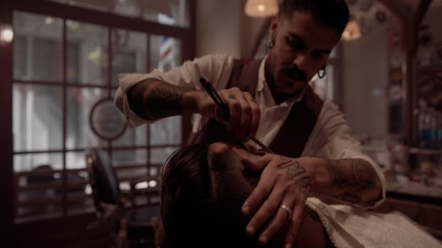 Young stylish old-fashioned barber shaving man with antique razor video