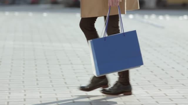 vídeos de stock, filmes e b-roll de mulher à moda nova que carreg seus sacos de compra através da cidade - boutique