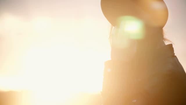 Joven elegante sombrero pasar tiempo en el centro de la ciudad en puesta de sol. Mujer disfrutando de la hermosa noche solo - vídeo