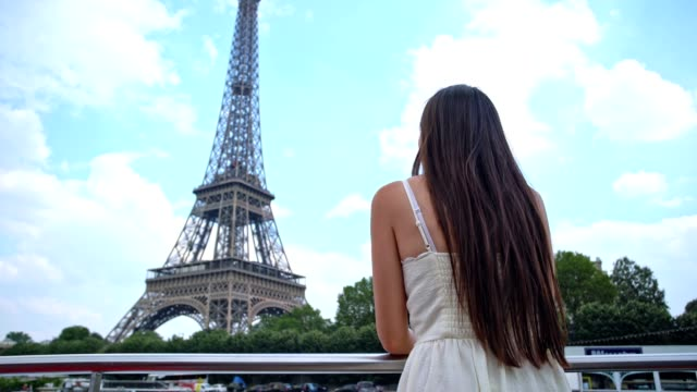 Young stylish woman looks on Eiffel tower