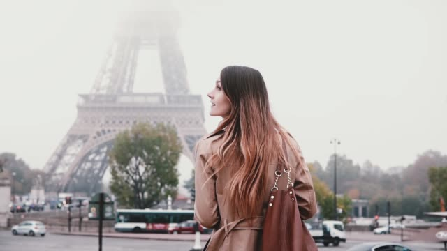 Young stylish woman taking photo of Eiffel tower in fog on smartphone. Girl traveling in Paris, France alone