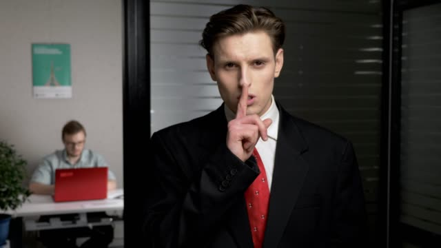 young successful businessman in suit showing a sign of silence. man works on a computer in the background. 60 fps - cisza filmów i materiałów b-roll