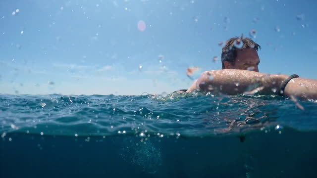 SLOW MOTION UNDERWATER: Young surfer man paddling on a surf in open water ocean video