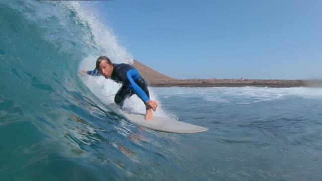 vídeos y material grabado en eventos de stock de cámara lenta: joven surfista montar tubo de la onda como cámara se sumerge en agua de mar clara. - surf