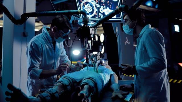 vídeos y material grabado en eventos de stock de el cirujano joven realiza una operación alienígena con la ayuda de equipos y herramientas. estas operaciones son visibles en el monitor. el experimento se lleva a cabo sobre un extraterrestre desde el espacio. - autopsia