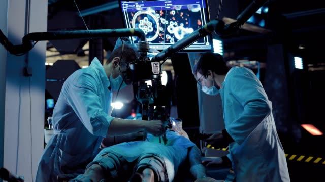 vídeos y material grabado en eventos de stock de el joven cirujano estudia el interior de una criatura alienígena. el técnico de laboratorio registra estas operaciones. unidad operativa del laboratorio espacial. - autopsia