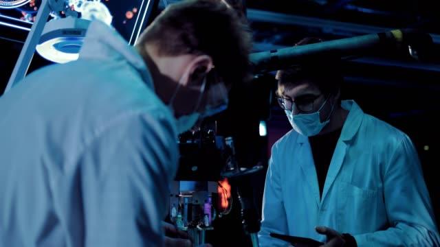 vídeos y material grabado en eventos de stock de jóvenes cirujanos trabajando en un experimento en el laboratorio. los dispositivos están conectados, los científicos llevan bata blanca y anteojos. - autopsia
