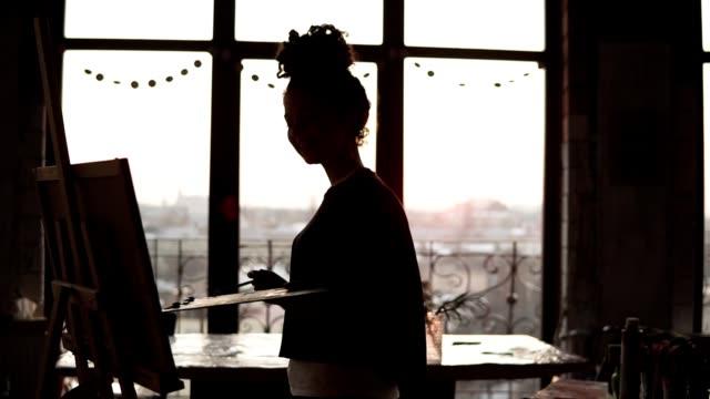 vídeos y material grabado en eventos de stock de joven artista femenina dulce bailando mientras su imagen con paleta en sus manos, en el estudio de arte estilo loft. - pintor artista