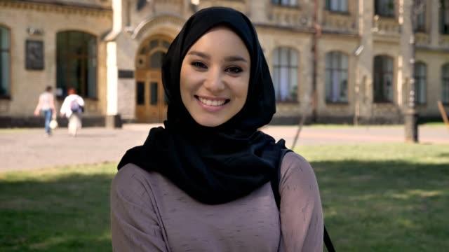 unga söta muslimsk flicka i hijab är stående och leende på dagtid på sommaren titta på kameran, bygga på bakgrund, religiuos koncept, känslomässiga koncept - hijab bildbanksvideor och videomaterial från bakom kulisserna