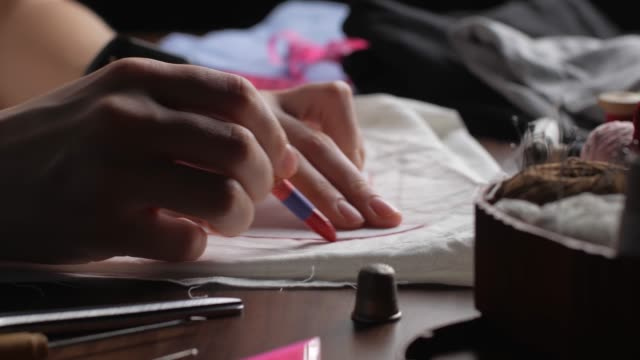 Young tailor uses red pencil to transfer patterns on white tissue. Close up womans hands drawing patterns on white cloth in late in evening in home. Young tailor uses red pencil to transfer patterns on white tissue. Close up womans hands drawing patterns on white cloth in late in evening in home. fabric swatch stock videos & royalty-free footage