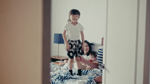 Young taiwanese girl joyfully jumps on the bed on Mothers Day (slow motion)