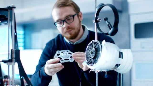 modern bir laboratuvarda genç yetenekli erkek mühendisi 3d yazıcı yardımıyla prototip yapıları. - model stok videoları ve detay görüntü çekimi