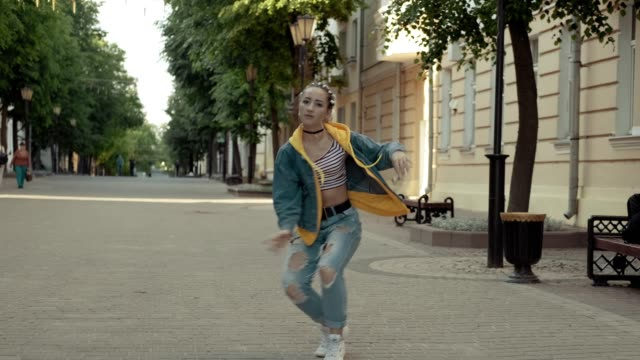 Young talented woman performing freestyle hip hop moves enjoying dance outdoors Young talented woman performing freestyle hip hop moves enjoying dance in slow motion. Attractive dancing girl in jeans with pigtails outdoors. Full length shot hip hop stock videos & royalty-free footage