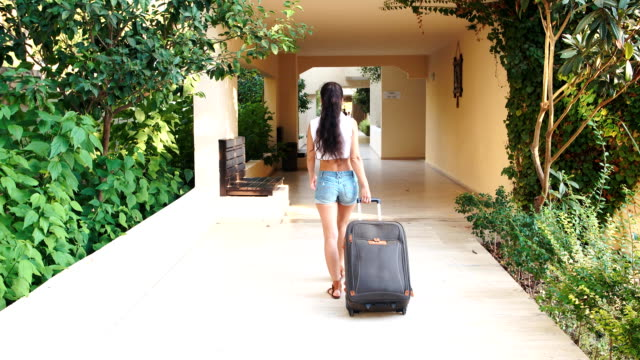 young tanned brunette woman in shorts, sunglasses comes with suitcase at hotel in summer. holiday and vacation video