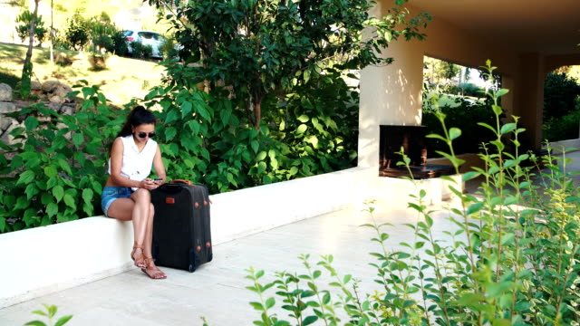 young tanned brunette woman in shorts, sunglasses with suitcase sitting and talking on phone in summer. video