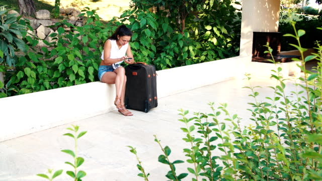 young tanned brunette woman in shorts, sunglasses with suitcase sitting and uses smartphone in summer. video